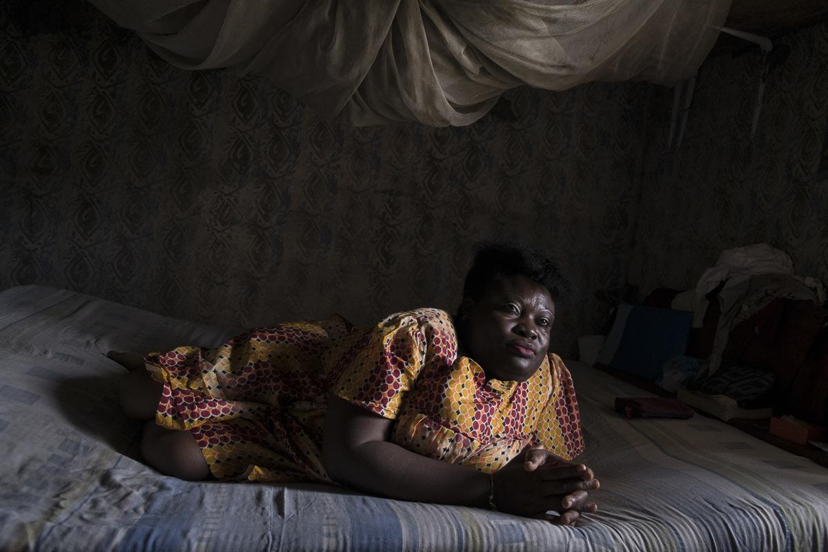 """Adrienne Surprenant - Hélène Ngo Honla, 42 ans, camerounaise Bassa. Elle est handicapée depuis l'âge de 5 ans, à cause de la poliomyélite, maladie qui entraîne une paralysie irréversible dans un cas sur deux cents. Elle ne peut plus marcher. """"J'ai bien marché. Maman m'a dit que je partais souvent à l'aube, chercher l'eau que je mettais sur la tête. Maman me racontait ça. Elle est morte il y a dix ans. Je la pleure encore. Une mère ne peut jamais rejeter son enfant."""